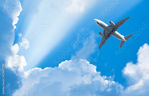 Canvas Print - plane is flying among clouds in rays of sun
