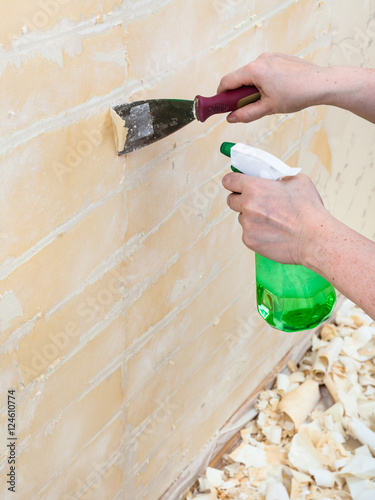 Removing Of Wet Old Wallpaper With Metal Spatula
