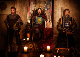 Medieval king with his queen and knights on guard in ancient castle interior