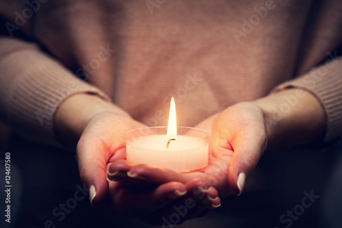 Fotografía  Candle light glowing in woman's hands. Praying, faith, religion