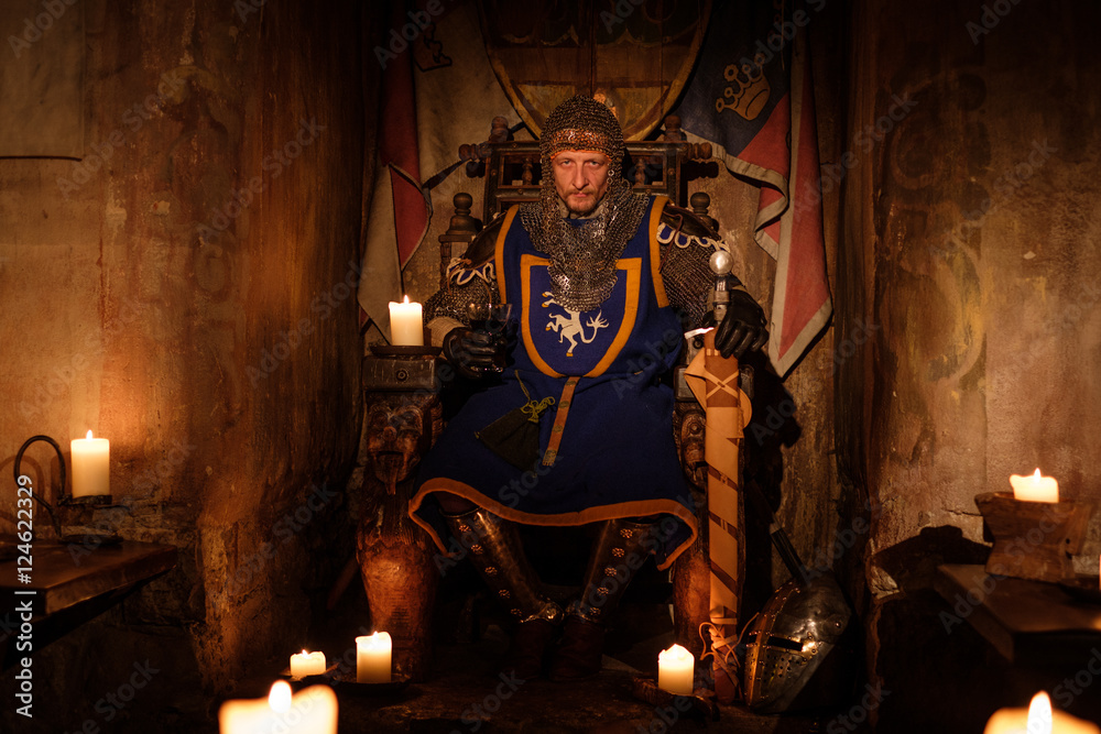 Fototapeta Medieval king on throne in ancient castle interior.