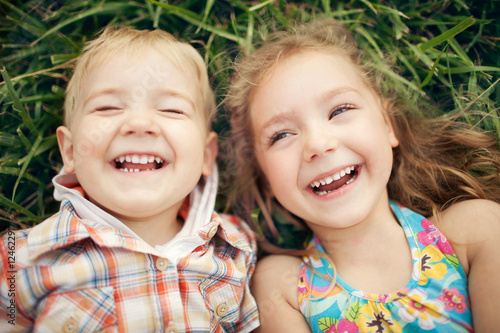 Fotografía  Above view portrait of two happy smiling kids lying on green grass
