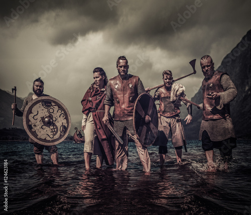 Photo A group of armed Vikings standing on river shore