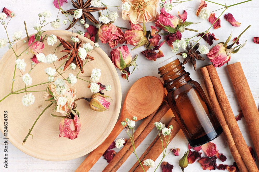 Fototapety, obrazy: Essential oil of rose, cinnamon, anise mix. Herbal aroma beauty care. Dropper bottle, dried fragrant flowers, sticks, wooden utensils, top view background.