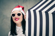 Portrait of a pretty girl in Santa Claus hat and sunglasses