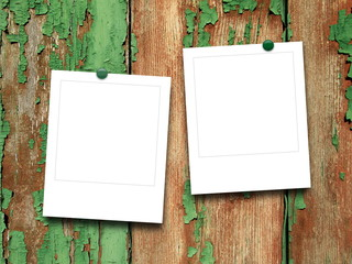Two blank square photo frames on green and brown scratched wooden boards background