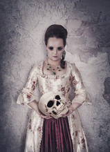 Witch Woman In Medieval Dress Holding Human Skull In Hands