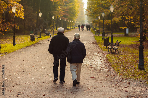 Foto  Elderly couple walking in park in autumn