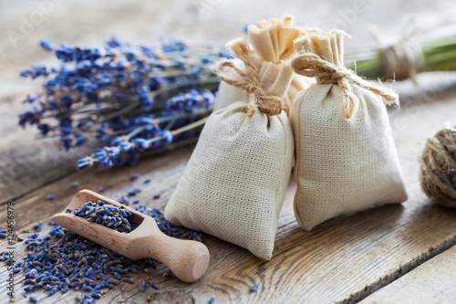 Bunch of lavender flowers and sachets filled with dried lavender - 124656979