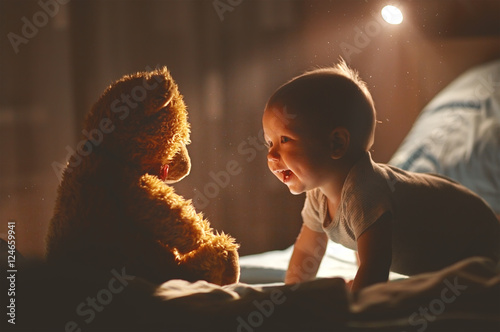 Photo  Happy baby laughing with teddy bear in bed