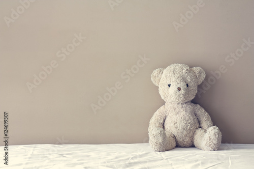 Fotografie, Obraz vintage teddy bear sit on the right side white bed at headboard