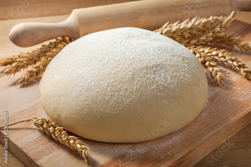 Fotografie, Obraz  Fresh dough on a board with ears of wheat and rolling pin.