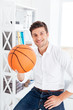 Handsome businessman sitting at the table and holding ball