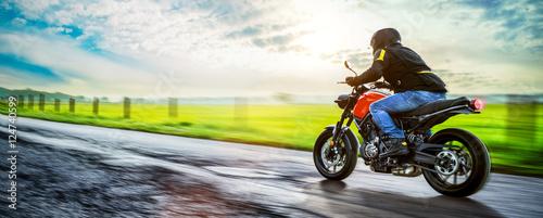 Fotografia, Obraz Motorrad fährt auf freier Landstrasse in den Sonnenuntergang