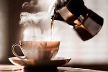 Pouring Espresso Coffee Into Coffee Cup From Moka Maker