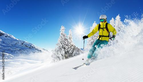 Skier on piste running downhill Fototapete