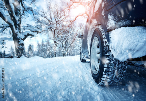Plakat  Car tires on winter road covered with snow
