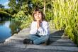 peaceful young yoga child enjoying relaxing, meditating near water