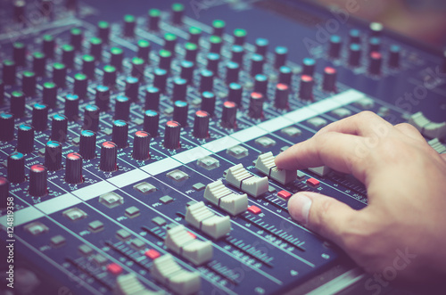 Fotografie, Obraz  Hand adjusting audio mixer