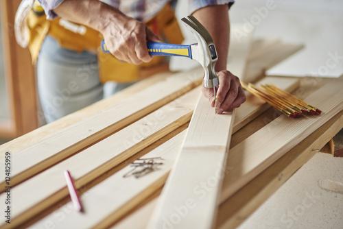 Fototapeta Hammering nails into wooden planks
