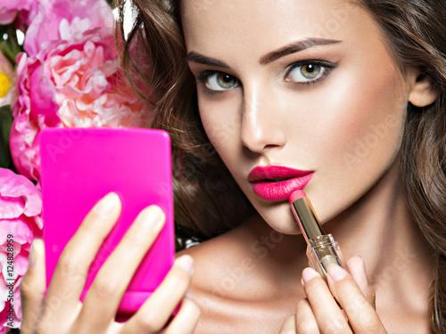 Fotografie, Obraz  Woman applying lipstick looking at mirror