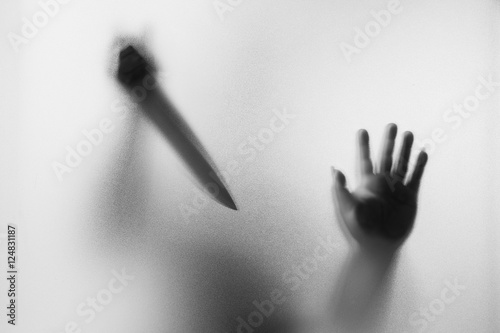 Fototapeta Horror Murderer. Dangerous man behind the frosted glass with a k