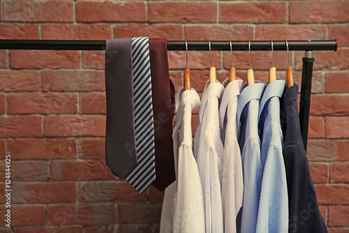 Hangers with male shirts and ties on clothes rail against