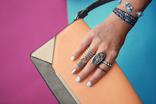 Female Hand With Jewelry And Clutch Bag On Color Background