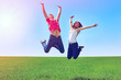 Happy active couple jumping in green field against blue sky