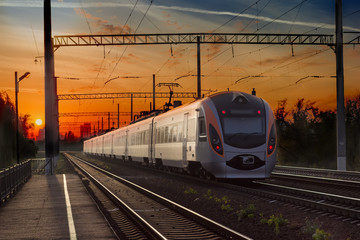 Passenger inter-city train in city on the sunset background