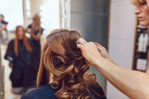 Hair stylist makes the bride before wedding