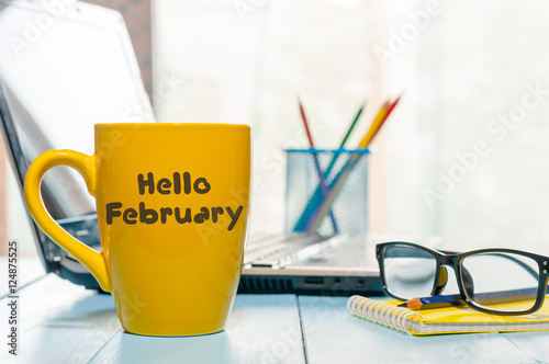 Obraz Hello February written on yellow coffee cup at business office background with empty space. Winter time - fototapety do salonu