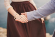 Guy in blue jacket and girl in beige and brown dress stand side by side holding hands. Shallow focus.