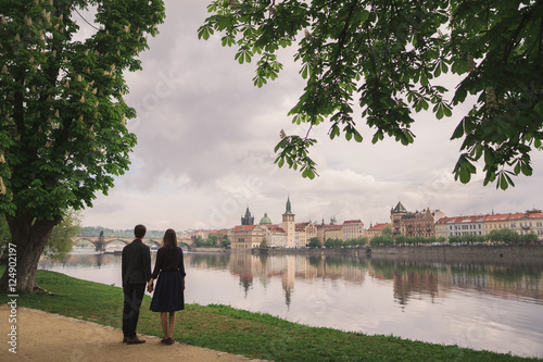 young couple holding hands and watching Prague cityscape from the riverside Wallpaper Mural