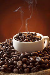 Fototapeta Kawa White cup and coffee beans on dark background, close up view