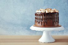 Chocolate Cake With Marshmallow On Plastic Stand On Wall Background