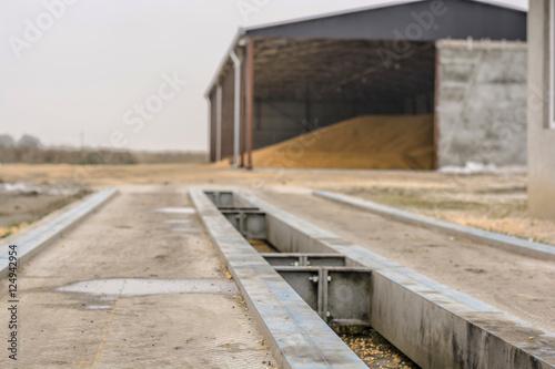 Fotografija  Trucking Weigh Station with grain tank in background
