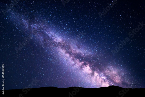 Foto op Canvas Zwart Milky Way and pink light at mountains. Night colorful landscape. Starry sky with hills at summer. Beautiful Universe. Space background with galaxy. Travel background