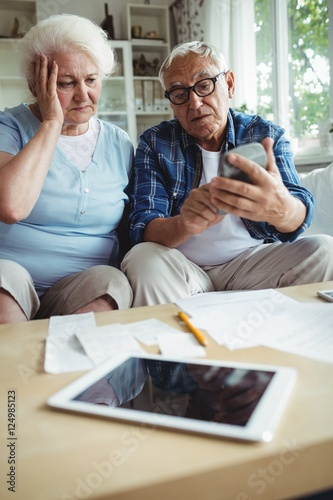 Fototapety, obrazy: Worried senior couple interacting while checking the bills