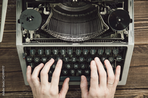 Fotografie, Obraz  Writer typing with retro writing machine. View from above.