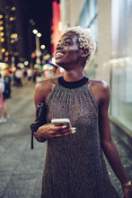 USA, New York City, Smiling Young Woman On Times Square At Night Watching Something