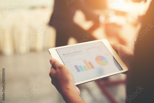 Foto  Business person hand holding financial statistics displayed on t
