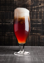 Glass Of Brown Ale Beer With Foam On Wood