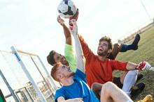 Three Football Players Holding A Ball