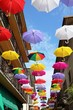 Many colorful floating umbrellas in an alley, Italy