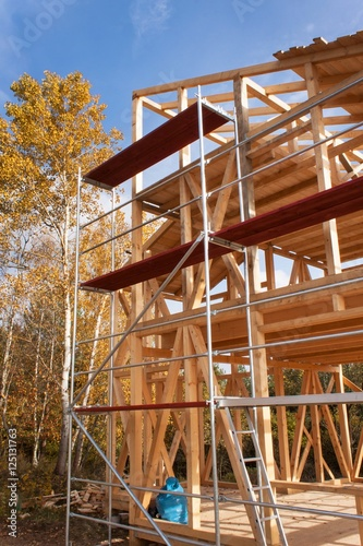 Poster Industrial geb. Metal scaffolding around the unfinished house. Construction of ecological house. Wooden frame of house under construction.Framed New Construction of a House. Timber house in building process