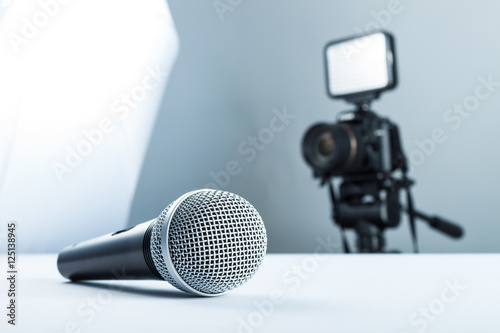 Obraz A wireless microphone lying on a white table against the background of the DSLR camera to led light. - fototapety do salonu