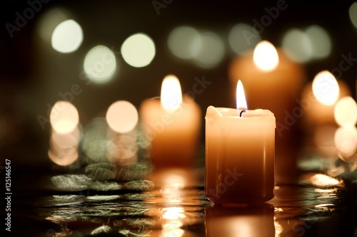 Burning candle with reflection against candlelight background Wallpaper Mural