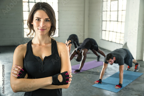 Fototapeta Small business owner of athletic gym smiling trainer instructor posing for a por
