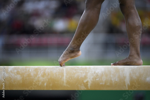 Tuinposter Gymnastiek Female gymnast on balance beam during competition